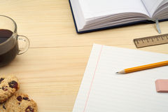 Workplace, office supplies, coffee cup and cookies on wooden table. Royalty Free Stock Images