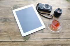 Workplace with office tools and gadgets. Cup of coffee on a table. Tablet, phone and camera to develop applications or. Other projects Stock Photos