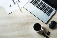 Workplace with open laptop and cup of coffee on office wooden desk table. Top view, copy space. Workplace with open laptop and cup of coffee on office wooden Stock Image