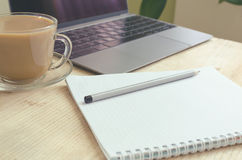 Blogger workspace - open laptop, notebook on spirals, pencil, cup of coffee. Side view. Toned image stock photography