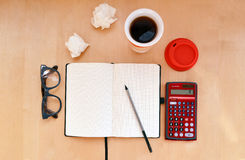 Workplace with open notebook, glasses, calculator and cup of coffee or tea on wooden desk. Creative workplace with open notebook, glasses, red calculator and cup Stock Photo