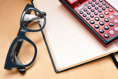 Workplace with open notebook, glasses and calculator. Workplace with open notebook, glasses and red calculator Royalty Free Stock Image