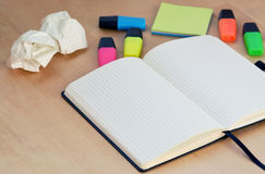 Workplace with open notebook and  highlighters on wooden desk. Creative workspace with open notebook and colorful highlighters on wooden desk Stock Photo