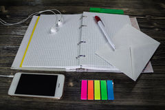 Workplace organisation: blank notepad with colorful stickers, pen and smartphone on hard wood table. Workplace organisation: blank notepad with colorful Stock Photo