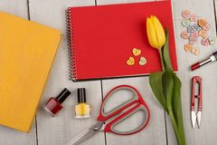 Flower tulip, blank red note pad, yellow book, scissors, nail polish and buttons in the shape of hearts. Workplace painter, designer or artist - Flower tulip Royalty Free Stock Photography