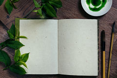 The workplace painter  and green leaves. The presentation. The blank notebook. Spring time blank notebook. Royalty Free Stock Photo