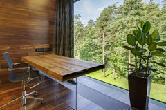 Workplace with panoramic window in luxury home. Modern workplace with panoramic window in luxury home Royalty Free Stock Photos
