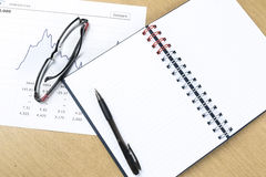 Workplace with pen, notebook, glasses and financial report Royalty Free Stock Images
