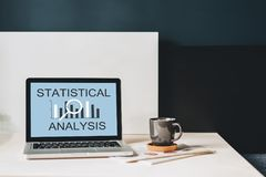 Workplace without people, close-up of laptop with inscription statistical analysis on screen on white table, desk. Nearby is closed paper notebook, pen Royalty Free Stock Image