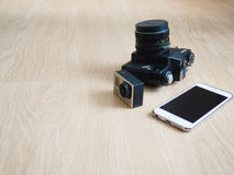 Workplace with photo camera and smartphone. Wooden background and different kinds of cameras Royalty Free Stock Photo