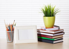 Workplace with photo frame, pencils, books Royalty Free Stock Image
