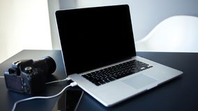 Workplace photographer and designer, laptop with camera and smartphone on the table. stock photography