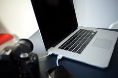Workplace photographer and designer, laptop with camera and smartphone on the table. stock photos