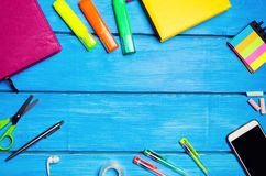 Workplace of the pupil of the school on a blue wooden table. Creative disorder, scattered pens and pencils. Place for text, nobody royalty free stock photos