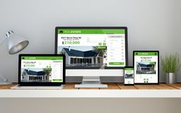 Workplace with real estate online responsive website on devices. A computer, laptop, smartphone and tablet on a desktop workspace with real estate online royalty free stock photos