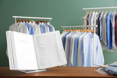 Workplace of receptionist with price list. At dry-cleaner`s stock image