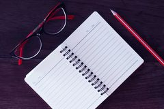 Workplace: Red glasses, note-book and pencil on a table Royalty Free Stock Image