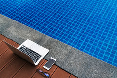 Workplace at the resort. Laptop and smartphone glasses near blue swimming pool. Modern Gadgets. Workplace at the resort Royalty Free Stock Images