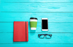 Workplace with school accessories and smartphone on blue wooden background. Top view and copy space Royalty Free Stock Photos