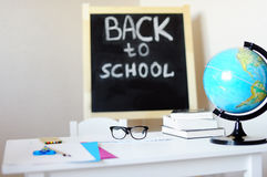 Workplace with school desk, blackboard, globe and eyeglasses Stock Image