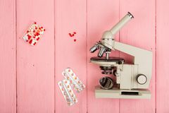 Workplace scientist doctor - microscope, pills on pink wooden table royalty free stock image