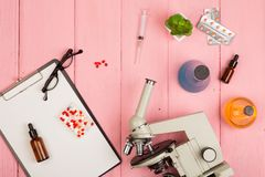Workplace scientist doctor - microscope, pills, syringe, eyeglasses, chemical flasks with liquid, clipboard on pink wooden table. Workplace scientist / doctor royalty free stock image
