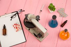 Workplace scientist doctor - microscope, pills, syringe, eyeglasses, chemical flasks with liquid, clipboard on pink wooden table royalty free stock photo