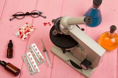 Workplace scientist doctor - microscope, pills, syringe, eyeglasses, chemical flasks with liquid on pink wooden table. Workplace scientist / doctor - microscope stock image