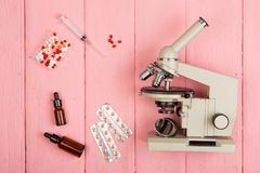 Workplace scientist doctor - microscope, pills, syringe on pink wooden table royalty free stock photos