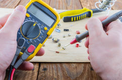 The workplace of serviceman. Hands holding the multimeter. Stock Photos