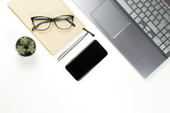 Workplace still life from above with laptop, notebook, black sma. Rtphone, small cactus, pen and glasses stock image