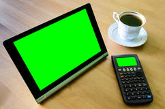Workplace with tablet pc - green box, calculator and cup of coff Stock Images