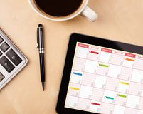 Tablet pc showing calendar on screen with a cup of coffee on a d Royalty Free Stock Images