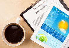 Workplace with tablet pc showing weather Stock Image