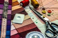 Workplace tailor. On the table close-up lie the samples of fabrics, scissors, thread, balac, roulette and buttons. stock images