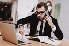 workplace Vestito di affari siedasi Parlando sul telefono immagine stock