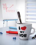 Workplace Wellbeing and Business Performance Conce. Close up of a mug where it is written I love my Job and a flipchart with a growing chart. Concept for Royalty Free Stock Photography