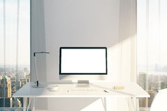 Workplace with white computer screen. Creative desktop with blank white computer screen in sunlit office with windows and city view. Mock up, 3D Rendering Royalty Free Stock Photos