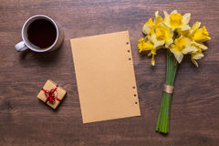 Workplace with white cup with tea, a gift with a red ribbon, paper and a bouquet of daffodils Royalty Free Stock Images