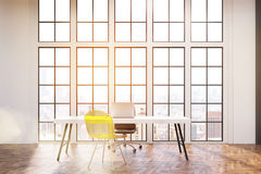 Workplace with white desk, an office chair and a transparent yellow visitor chair. Royalty Free Stock Images