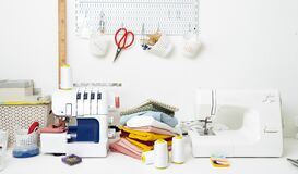 Workplace: White table with a sewing machine and an overlock for sewing.
