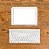 Workplace with white tablet computer and keyboard. Royalty Free Stock Photos
