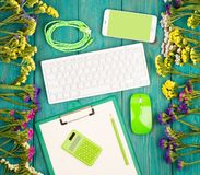 Workplace with wireless slim keyboard, green mouse, smart phone, clipboard, calculator, blank yellow stock photography