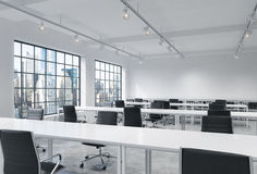 Workplaces in a bright modern loft open space office. Empty tables and docents' book shelves. New York panoramic view. A concept o Stock Photos