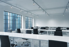 Workplaces in a bright modern loft open space office. Empty tables and docents' book shelves. Singapore panoramic view. A concept Royalty Free Stock Images
