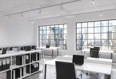 Workplaces in a bright modern loft open space office. Tables equipped with laptops; corporate documents' shelves. New York in the Royalty Free Stock Photography
