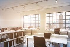 Workplaces in a bright modern loft open space office. Tables equipped with laptops; corporate documents' shelves. New York in the Stock Images