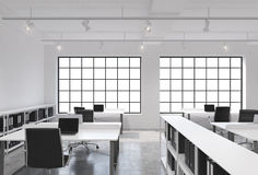 Workplaces in a bright modern loft open space office. Tables equipped with laptops; corporate documents' shelves. White copy space Stock Images