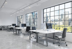 Workplaces in a bright modern loft open space office. Tables are equipped with modern computers; book shelves. New York panoramic Royalty Free Stock Photography