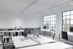 Workplaces in a bright modern loft open space office. Tables are equipped with modern computers; book shelves. New York panoramic Royalty Free Stock Photos